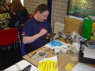 André creatief aan het werk met verf en papier